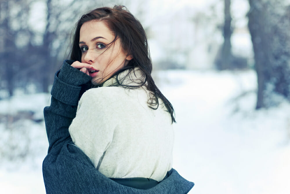 Girl in the snow glancing over her shoulder